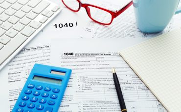 Income tax return form with computer keyboard calculator and notebook
